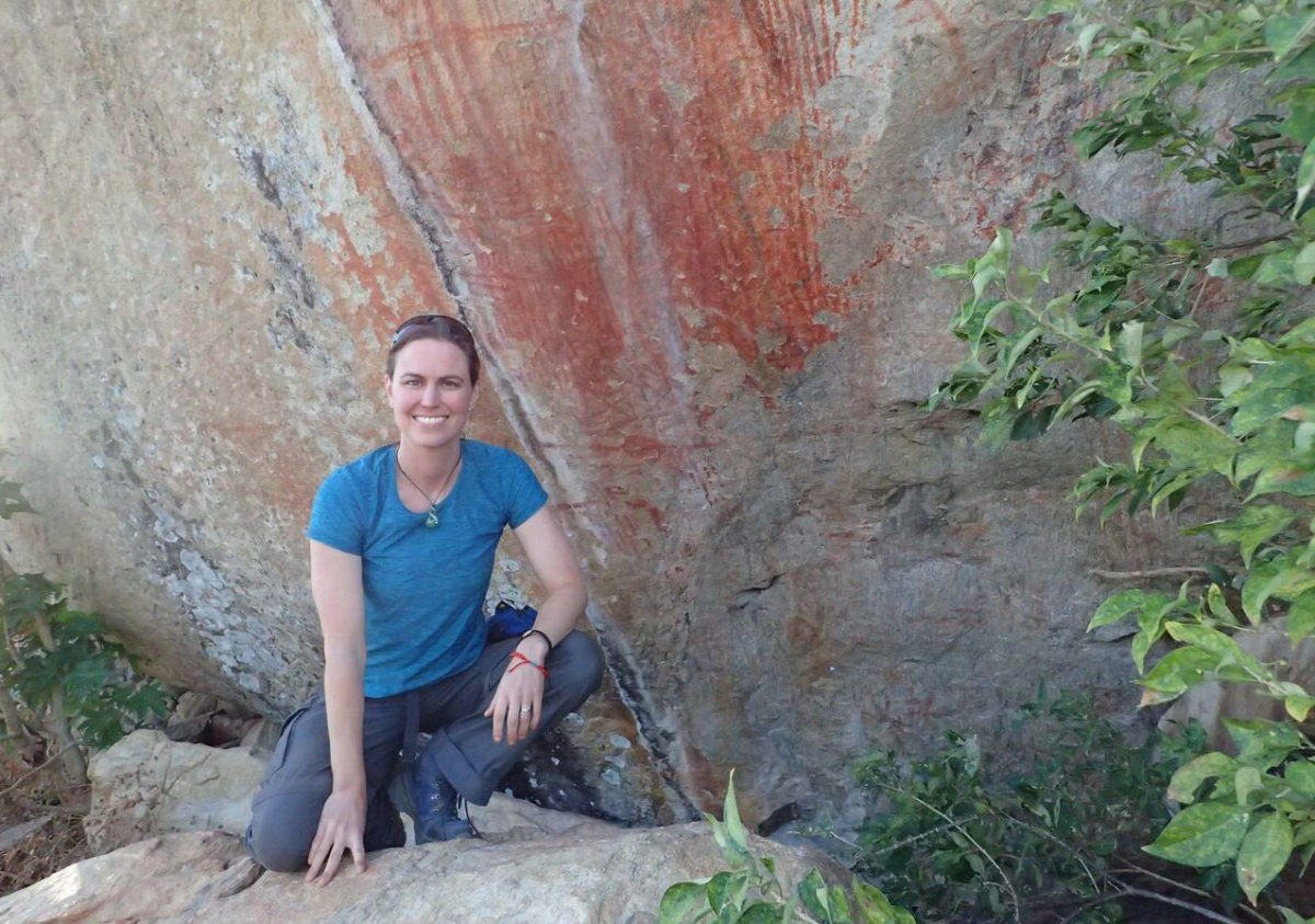 Emory anthropologist Jessica Thompson next to Malawi rock art paintings.