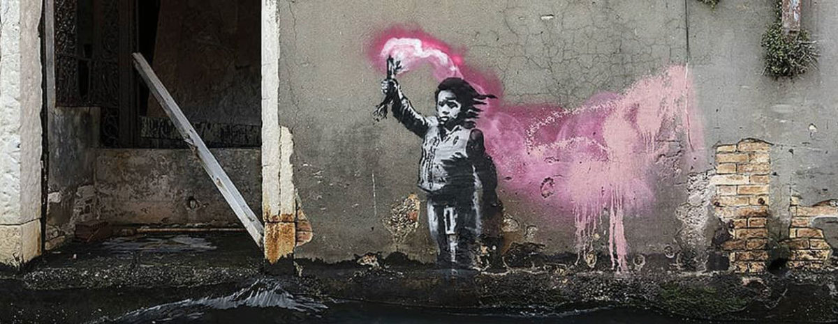 The mural depicts a migrant child holding a pink flare. Photo Credit: @banksy/Designboom.