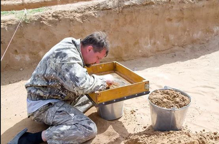 A member of the team  led by Georgiy Stukalov, an archaeologist at the Astrakhan State Museum, sifts the dirt from the kurgan, searching for archaeological remains. Photo Credit: Ministry of Culture and Tourism of the Astrakhan Region/Live Science.