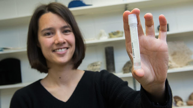 Assistant Professor Clara Blattler with a vial of seawater dating to the last Ice Age — about 20,000 years ago. Credit: Jean Lachat