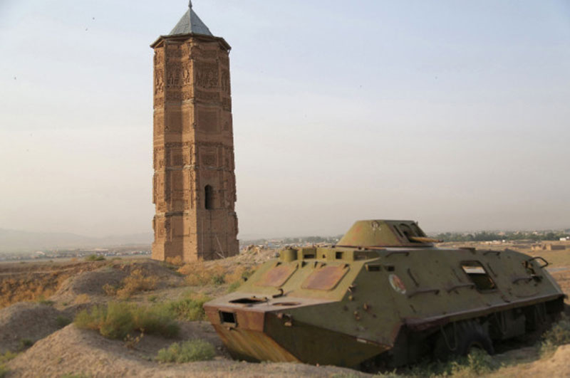 A destroyed Russian tank is seen alongside one of two minarets built in the 12th century in Ghazni city. Photo Credit: Getty Images/BBC.