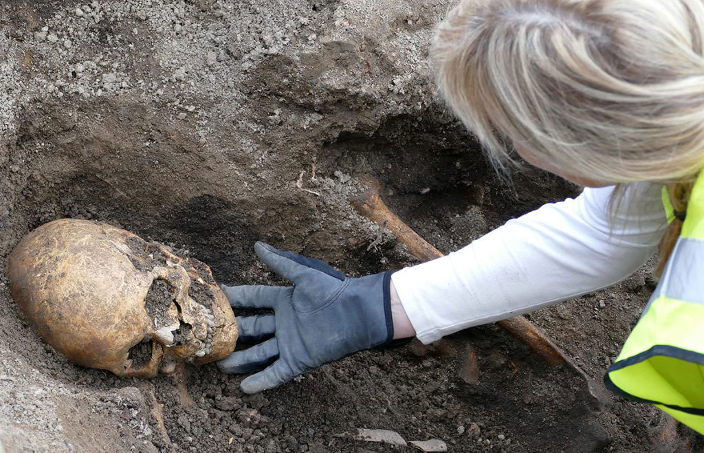 Osteologist Carolin Arcini examines the skeleton of a man from intact boat grave. Photo Credit: Arkeologerna Statens Historika Museer/The History Blog.