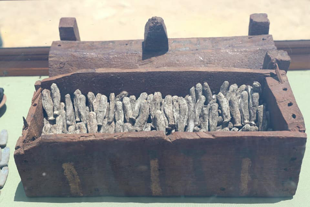 Wooden box filled with ushabti statuettes.