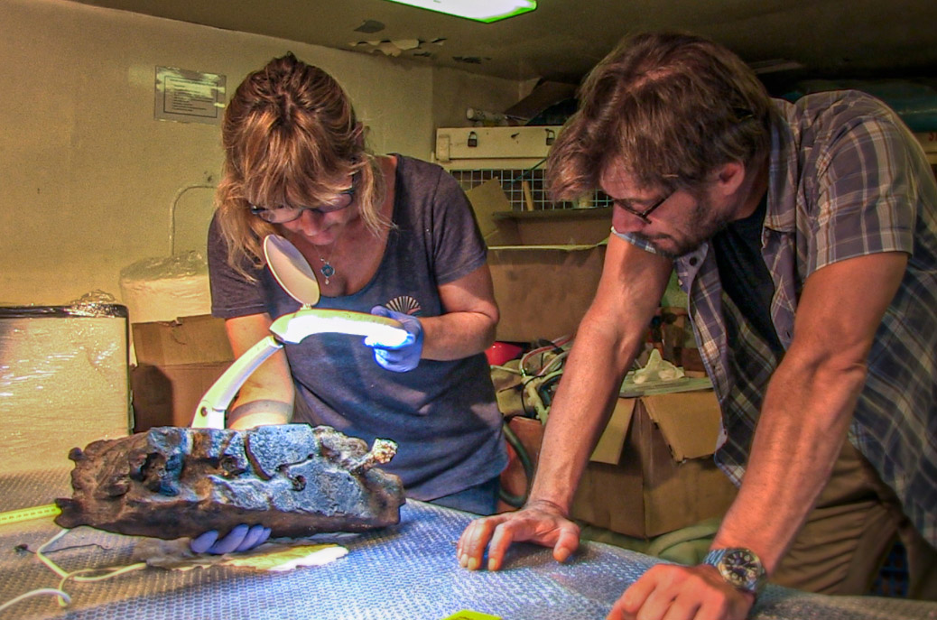 Scientific head of research Dr George Koutsouflakis and head of the conservation department of the Ephorate of Underwater Antiquities Chrysa Fouseki examine a boat's wooden section with bronze nails recovered from the Antikythera shipwreck (photo: MOCAS).
