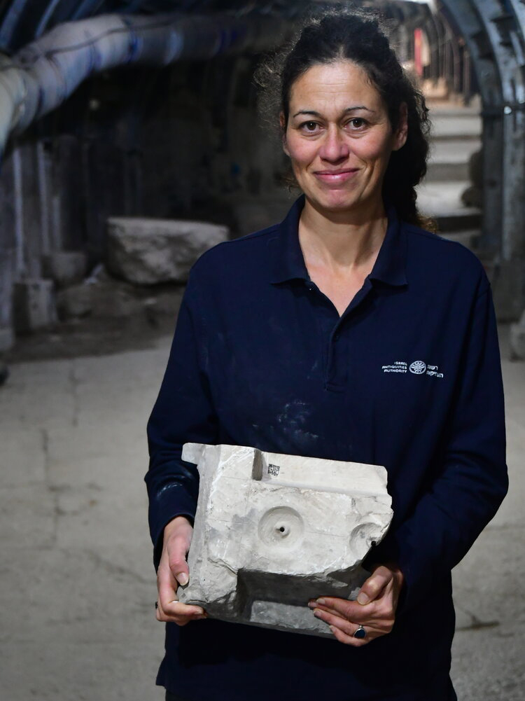 Bottom of the table portion, held by IAA archaeologist Hélène Machline. Photo: Ari Levi, Courtesy of the Antiquities Authorities Authority.