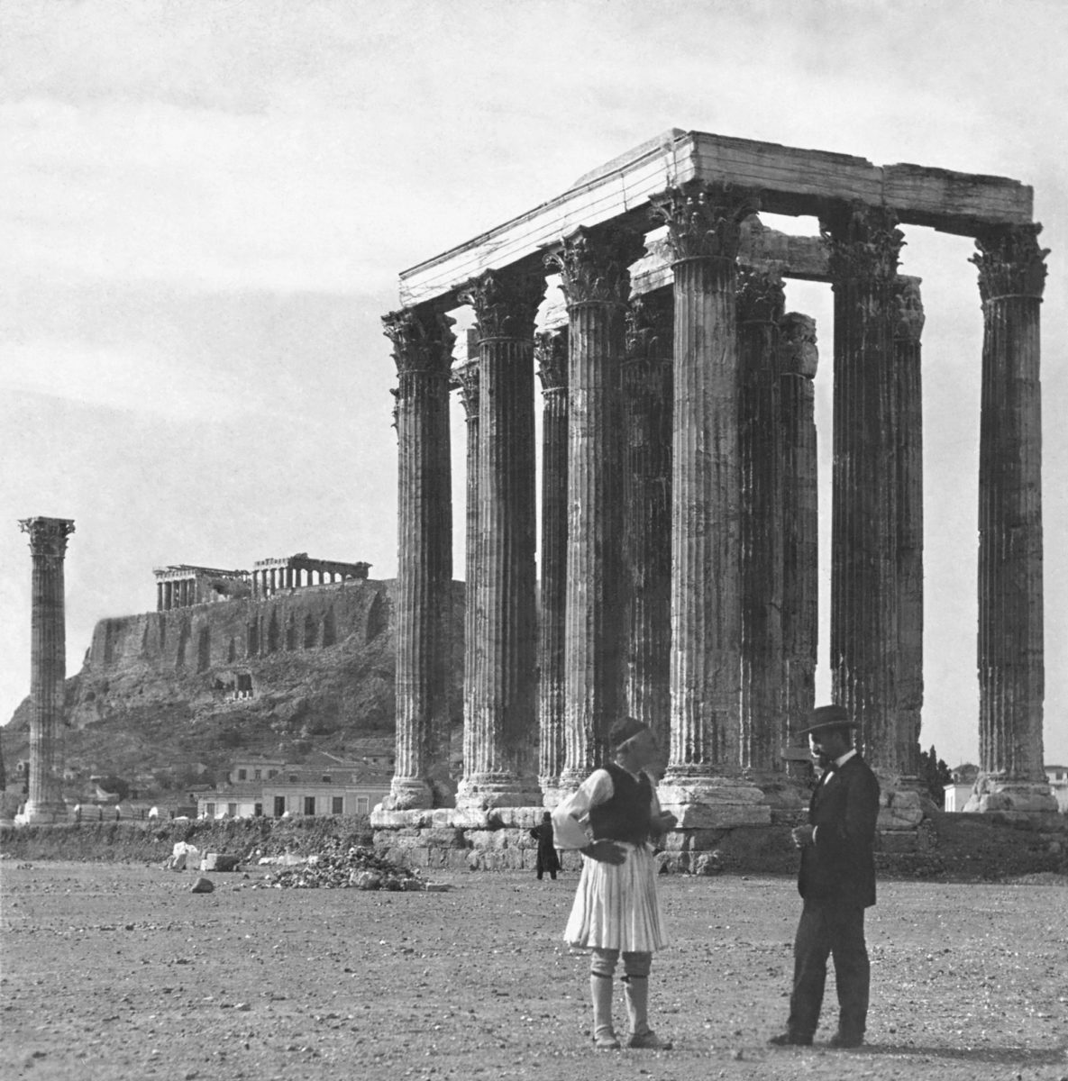 A guard in traditional Greek dress and a middle-class Athenian dressed in the manner talk in front of the temple of Olympian Zeus. Late 19th, early 20th century. Photographer unknown. Courtesy of the Library of Congress