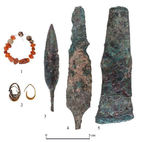 Weapons and jewellery found near the temple inner sanctum: beads, earrings, an arrowhead, a dagger and an axe head. Credit: T. Rogovski.