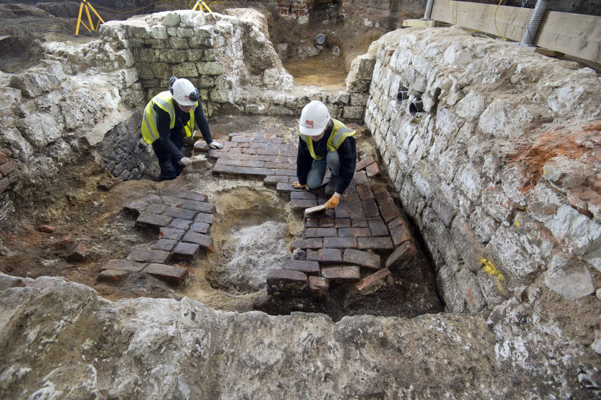 MOLA archaeologists excavating the top of the cesspit, which had been backfilled and covered over with several layers of brick flooring © MOLA