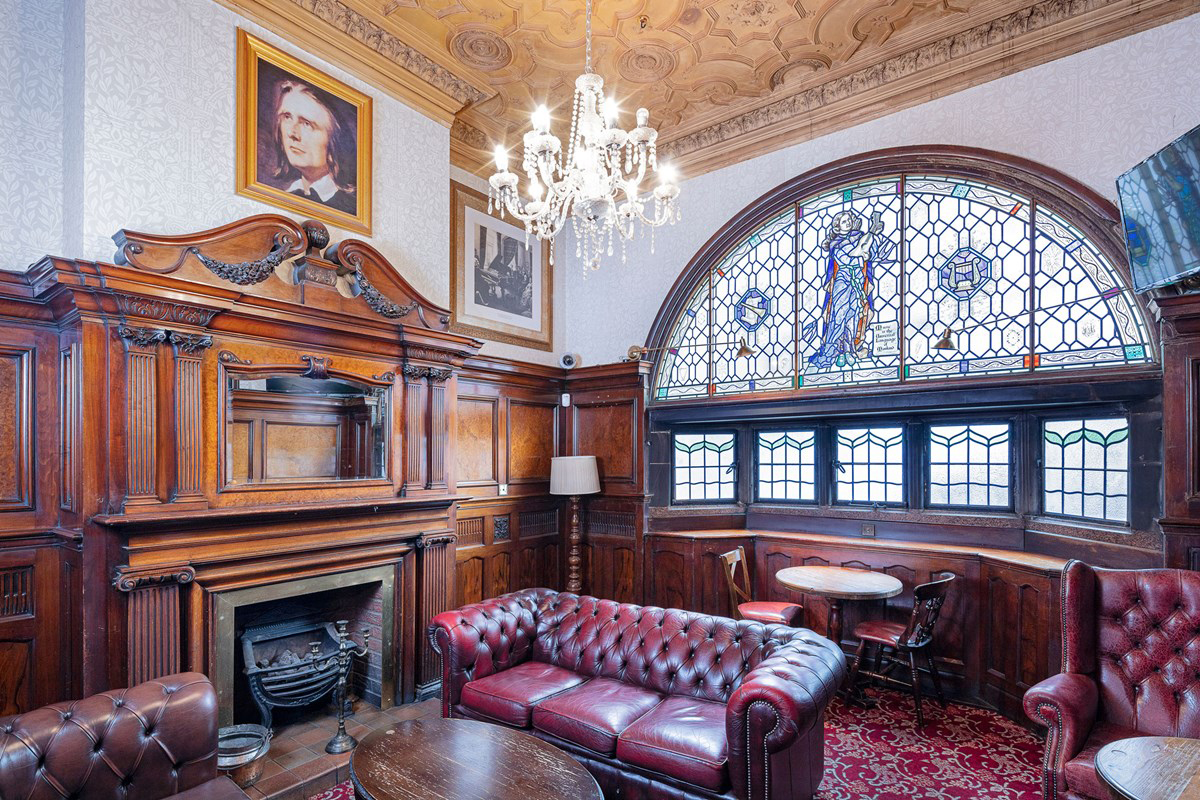 Interior of the Philharmonic Dining Rooms, Liverpool featuring a snug room with ornate hard wood fire surround and large decorative stained glass window to the street. © Historic England Archive, photographer credit Alan Bull, image reference DP234387