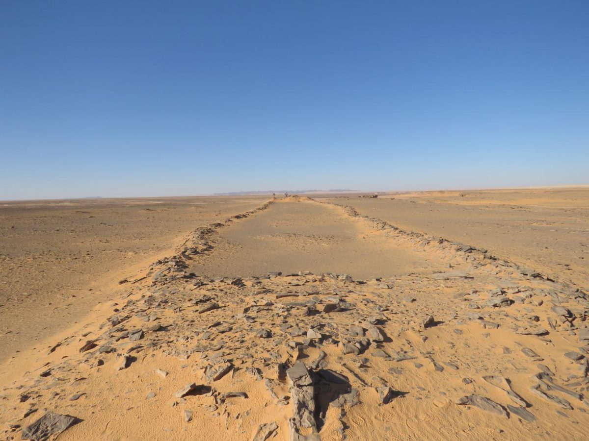 New archaeological research in Saudi Arabia documents hundreds of stone structures interpreted as monumental sites where early pastoralists carried out rituals. Image shows character of these structures as two platforms connected by low walls, note researchers at far end for scale. Credit: Huw Groucutt