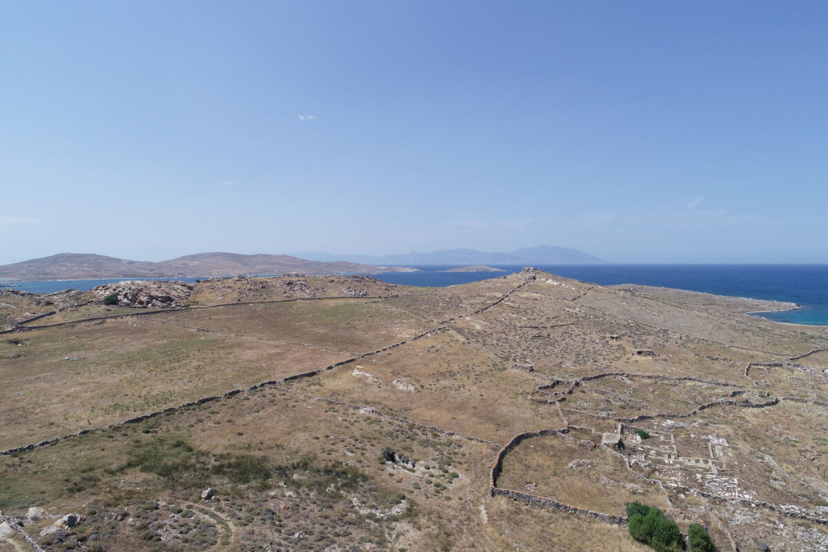 The Hellenistic necropolis of Delos on Rheneia, the pyramid shaped hill of Chomasovouni where the site of the Artemision on the island is likely to be. To the left, an ancient farmhouse next to a modern one. In the background, the northern part of Rheneia and Tinos on the horizon. (photo: MOCAS)