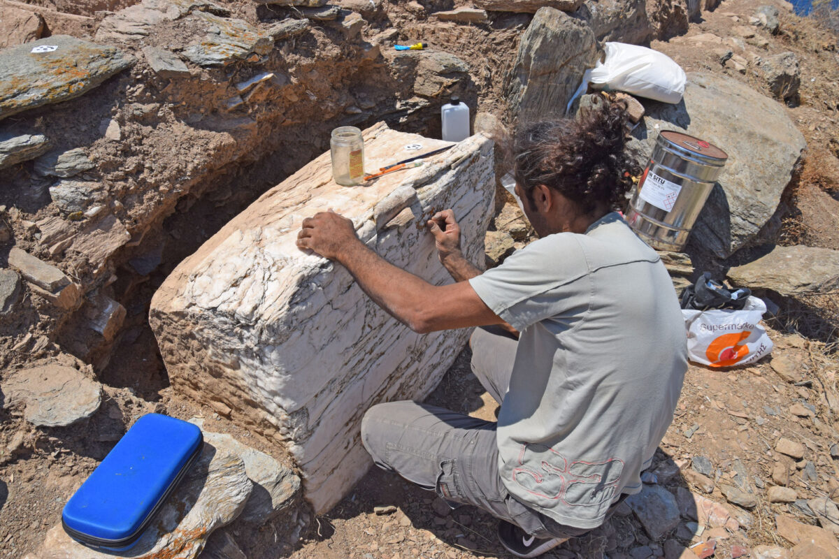 Fig. 14. Marble pedestal of statue embedded in Early Christian fortification wall (seen here during stabilizing work on the monument by conservator Lefteris Kosmides).