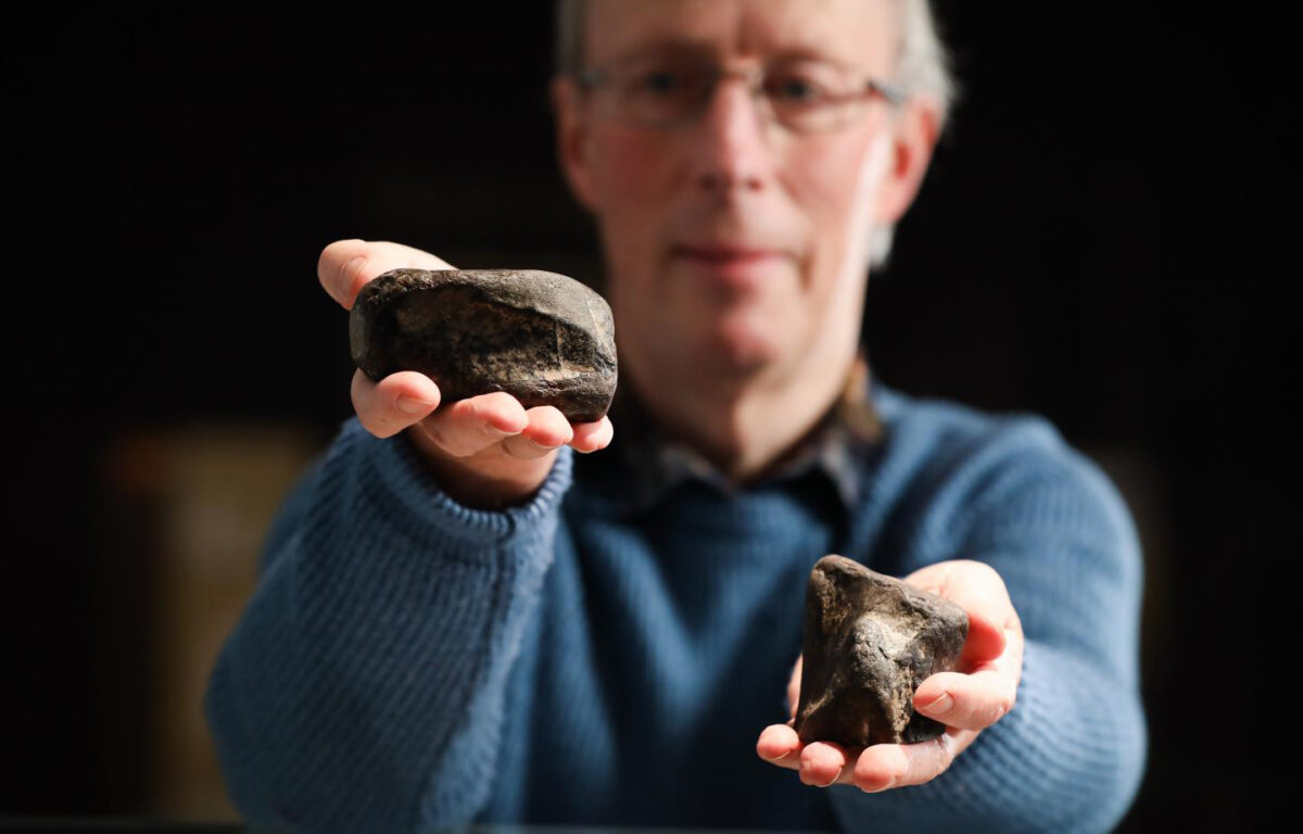 Dr Mike Simms, of National Museums NI, with the theropod tibia on the left and the Scelidosaurus femur on the right. Image Credit : National Museums NI