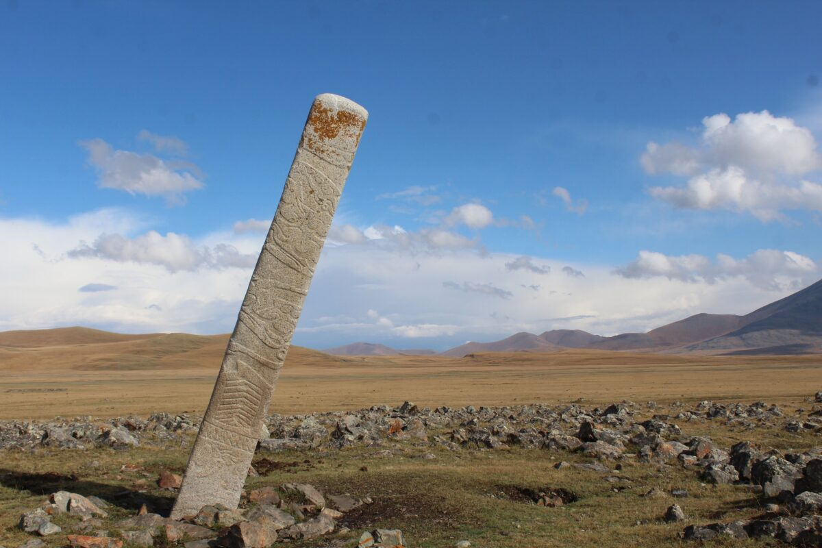 A leaning Deer Stone placed in front of dozens of small stone mounds containing ritually-sacrificed horse burials at the Bronze Age monument site of Ikh Tsagaanii Am, Bayankhongor Province, central Mongolia Credit: William Taylor