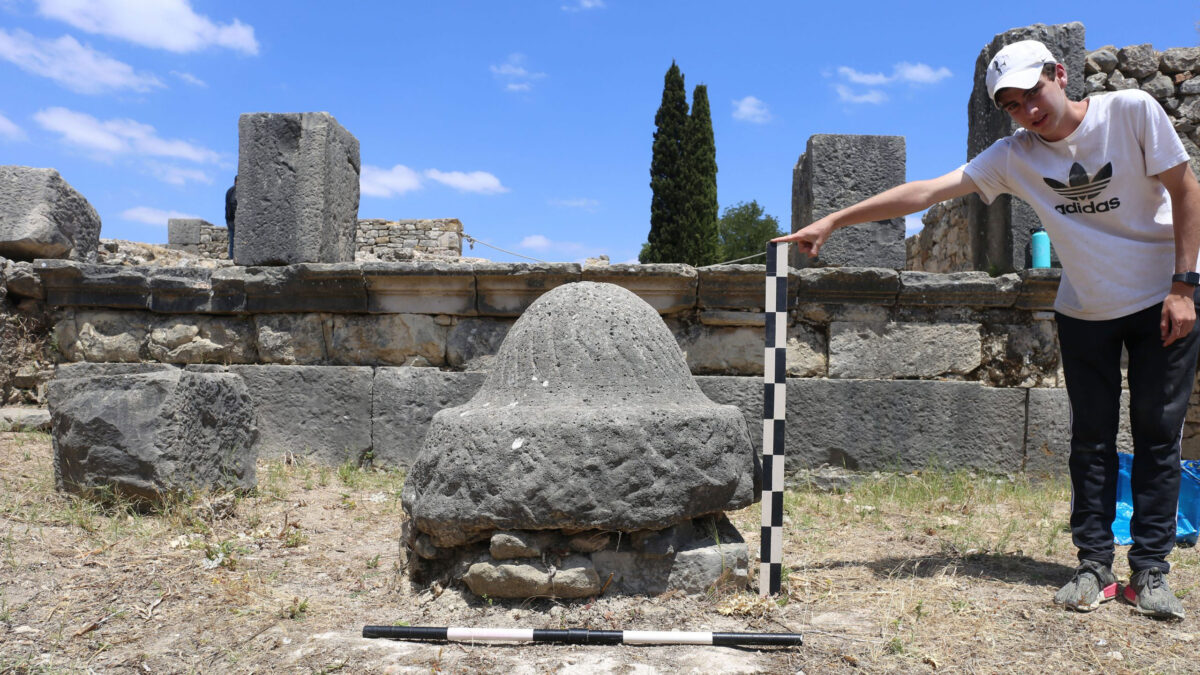 An olive millstone in Volubilis. Research assistant Drew Messing holds a tool for scale. Credit: Jared Benton.